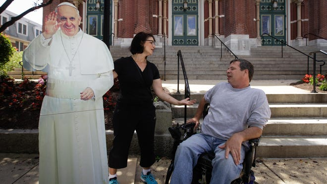 Christa Scalies and Paul Tanner use a cardboard cutout of Pope Francis to approach people in Wilmington and Philadelphia to discuss religion, life and the Pope's visit.