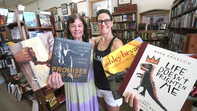 Janet Bollum, owner of The Muse Bookshop, and her daughter, Ella Ran, hold copies of some of the children's books on race and diversity that they will live stream readings of every Wednesday, beginning June 17. Ran and Renee Stewart, who co-own a shop at the back of The Muse, wanted to find a way to continue important discussions stemming from George Floyd's death.