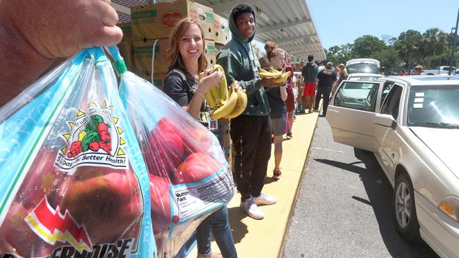 In this May 4, 2018 file photo, an army of volunteers load groceries into a long line of cars as Provision Packs and Second Harvest Food Bank partner together to provide the Holly Hill community with free groceries at the Holly Hill School.