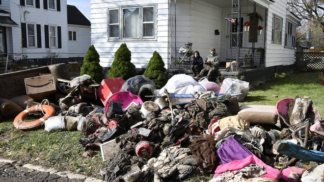 Residents on Gardner Street in Whitesboro clean up from the Halloween night flooding event last year.