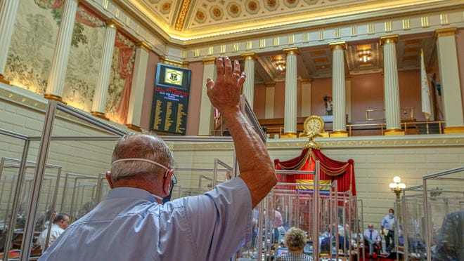 """Rep. Samuel Azzinaro, D-Westerly, votes on the House floor Thursday night. The General Assembly voted on a litany of bills in the short special session, from firefighter disability pensions to the removal of """"Plantations"""" from state's name."""