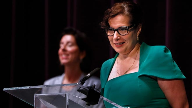 R.I. Education Commissioner Angélica Infante-Green listens to a question about Rhode Island's plans for opening schools, with Gov. Gina Raimondo in the background, during Wednesday's coronavirus briefing at Veterans Memorial Auditorium.
