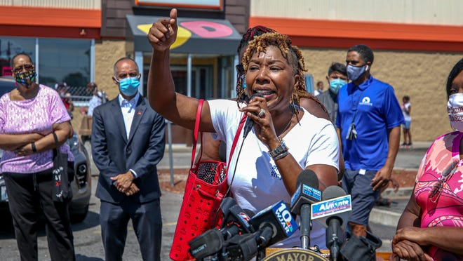 Shawndell Burney-Speaks tells the gathered crowd of her son Devin Burney's death by drive-by shooting in 2017. Mayor Jorge Elorza stands in the background at left.