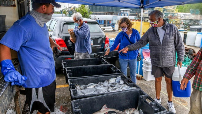 Seth Kourtesis, left, sells the morning haul directly to customers in the lot at Pier 9, in Newport, while his dad, Jon Kourtesis, does maintenance work back on his boat, the F/V Christopher Andrew.