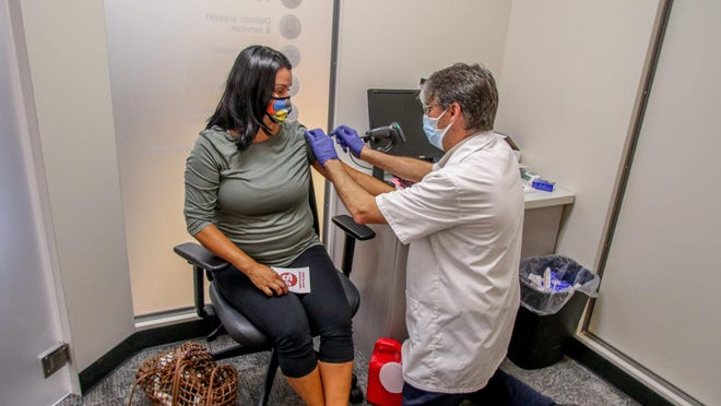 Rhonda McBurney, of Providence, gets her flu shot from pharmacist Joe Sayles in the HealthHUB inside CVS Pharmacy on Hope Street in Providence.