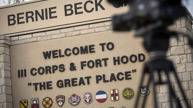 FILE - In this April 2, 2014, file photo, members of the media wait outside of the Bernie Beck Gate, an entrance to the Fort Hood military base in Fort Hood, Texas.