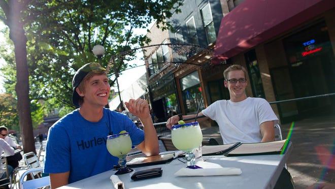 UI students Marcus Tatam (left) and Ryan Tegrootenhuis have a drink in the outdoor seating area at The Saloon Sept. 9, 2011, in downtown Iowa City.
