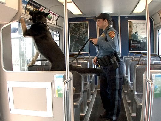 NJ Transit Police Officer Elaine Donnadio works with her dog Bosco aboard a light rail train at the Hoboken terminal Monday morning.