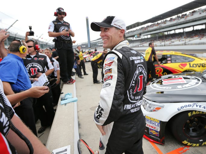 NASCAR driver Kevin Harvick is all smiles moments after climbing out of his car after winning the pole at the Indianapolis Motor Speedway on Saturday, July 26, 2014. Harvick broke the track qualifying record with a speed of 188.470.