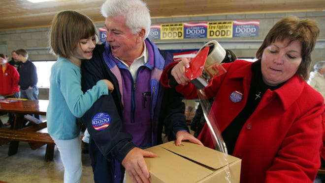 Sen. Chris Dodd and his daughter Gracie, 6, laugh as they get help from Peg Buman to tape up a care package they made to send to Iowa National Guardsmen that have been deployed overseas. Over the holidays in 2007, candidates left the campaign trail for just a single day, on Christmas.