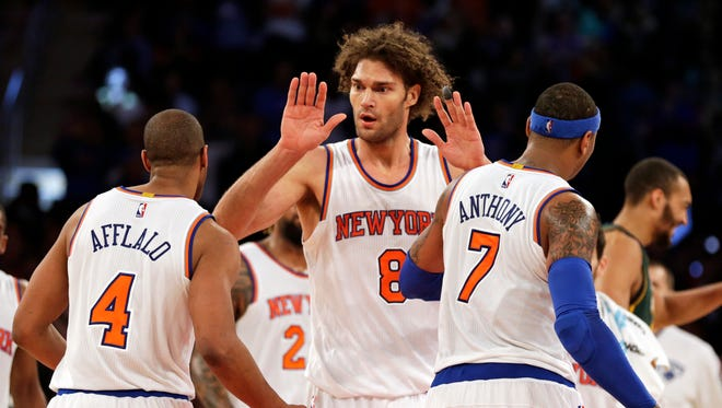 New York Knicks center Robin Lopez (8), Arron Afflalo (4), Carmelo Anthony (7) celebrate against the Utah Jazz during the second half of an NBA basketball game at Madison Square Garden. The Knicks defeated the Jazz 118-111 in overtime.