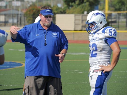 """Head coach Matt Dollar gives instructions to Kevin Galvan during a Fillmore practice. """"He was always a real strong kid,"""" says Dollar of Galvan. """"Then last year, he elevated to being a guard and linebacker for us. He was our MVP and this year, he's been lighting it up on defense."""""""