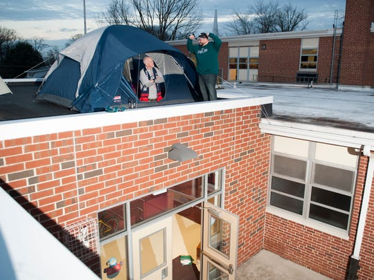 """Sam Sassano, principal of Glenview Elementary School in Haddon Heights and Patriots fan, in tent, and guidance counselor Matt Baals, an Eagles fan, made a """"gentleman's agreement"""" over who would win the Super Bowl. The loser would spend the night in a tent on top of the school. Sassano lost. But in a twist, both men camped out on the school's roof in separate tents on Thursday night, after a fundraiser supporting the school's service project program topped $3,450."""
