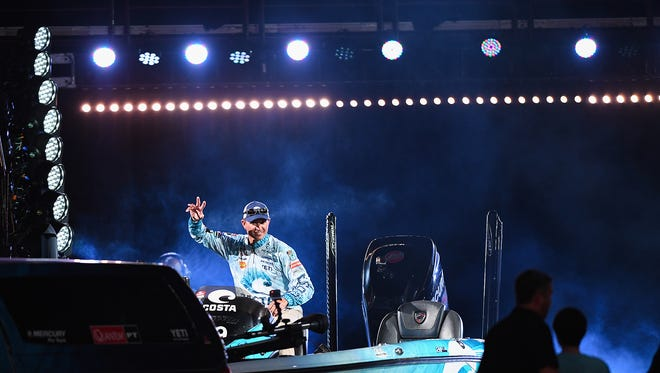Casey Ashley waves as he enters Bon Secours Wellness Arena in his boat during weigh in of the Bassmaster Classic tournament on Friday, March 16, 2018 at the