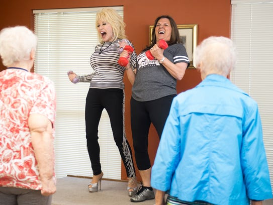 Dolly Parton, left, joins in on an exercise class at
