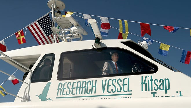 Gov. Jay Inslee stands in the pilot house of Kitsap Transit's passenger-only ferry, Rich Passage 1, during a ceremony Wednesday promoting the beginning of cross-sound service on Monday.