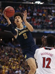 Michigan Wolverines forward D.J.Wilson scores against Louisville forward Mangok Mathiang during the second round of the 2017 NCAA tournament Sunday, March 19 at Bankers Life Fieldhouse in Indianapolis.