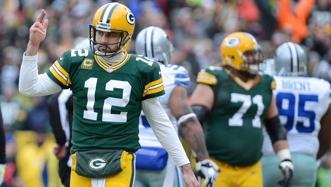 Packers quarterback Aaron Rodgers (12) celebrates his first-quarter touchdown pass against the Cowboys last January.