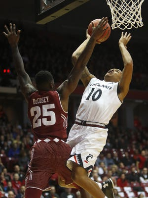 Cincinnati guard Troy Caupain goes up for a shot against Temple's Quenton DeCosey in the first half.