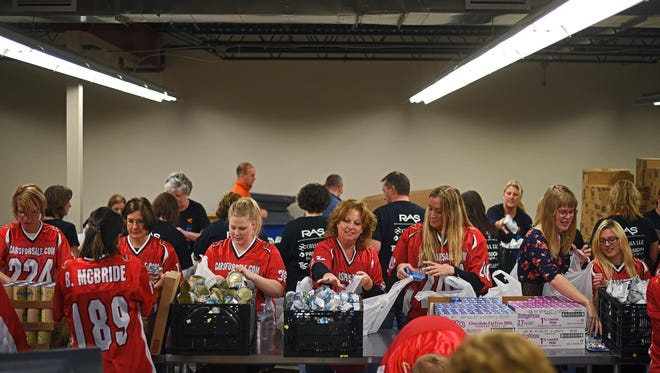 Volunteers bag food for Feeding South Dakota's BackPack Program, which aims to fill the hunger gap for children who might not have easy access to food over the weekend when not at school, Tuesday, Nov. 15, 2016, at Feeding South Dakota in Sioux Falls.