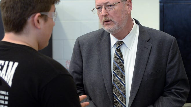 Pennsylvania Department of Labor and Industry Secretary Jerry Oleksiak, right, talks with a student in Erie, Pa.