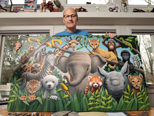 """Loren Long holds the """"Zoo Babies"""" painting that was"""