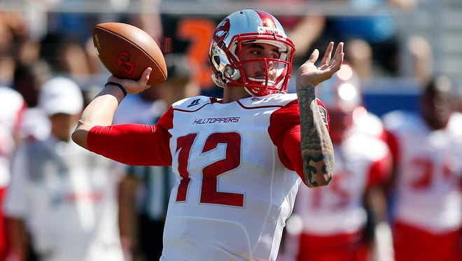 Oct 18, 2014; Boca Raton, FL, USA;  Western Kentucky Hilltoppers quarterback Brandon Doughty (12) drops back to pass in the first quarter of a game against the Florida Atlantic Owls at FAU Football Stadium. Mandatory Credit: Robert Mayer-USA TODAY Sports