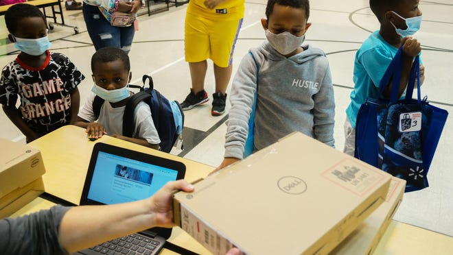 From left, first-grader DeMonte Morrow, 7, kindergartner Dekhai Morrow, 5, second-grader Masen Stewart, 7 and second-grader Devarrion Morrow, 8, pick up their computers before the start of the school year on Sept. 2 at Southwood Elementary School.