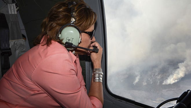 New Mexico Governor Susana Martinez looks out the window of a Black Hawk helicopter flying over the Dog Head Fire Thursday, June 16, 2016 in Albuquerque, N.M. Firefighters struggled Thursday to make progress against a fast-moving wildfire in central New Mexico as it consumed tinder dry forest, sent up a towering plume of smoke that could be seen for miles, and forced more residents from their homes.