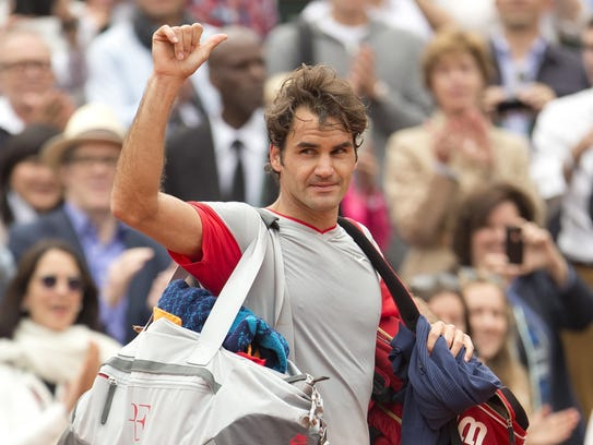 Jun 1, 2014; Paris, France;  Roger Federer (SUI) waves to the crowd as he leaves the court after his match against Ernest Gulbis (LAT) on day eight at the 2014 French Open at Roland Garros. Mandatory Credit: Susan Mullane-USA TODAY Sports