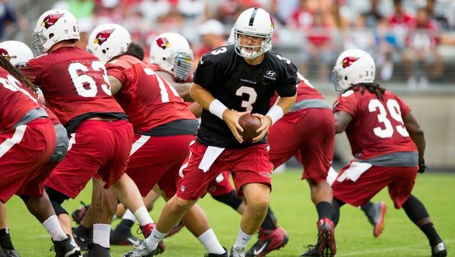 Cardinals quarterback Carson Palmer runs a play during training camp at University of Phoenix Stadium on July 26, 2014.