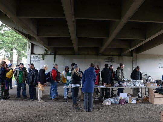 Volunteers offer food and supplies to the homeless under the Marion Street bridge during a previous count.