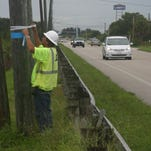 In a 2014 photo, survey foreman Randy Scott marks a utility pole in preparation for a three-year construction project to widen Barnes Boulevard in Rockledge and improve drainage.