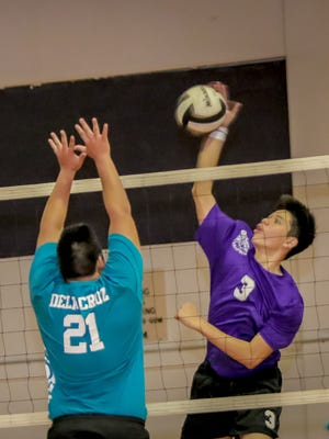Brendan Santos (3) of George Washington High School delivers a spike over the net.