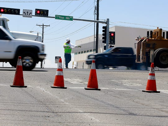 A worker directs traffic while crews lay down pavement on Thursday on East Piñon Hills Boulevard.