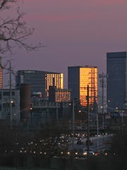 Louisville's skyline glows in the setting sun as traffic flows westbound on Interstate 64 in the Portland neighborhood.