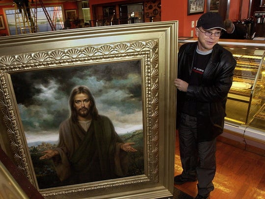 In this 2002 photo, Jim Bakker holds one of the paintings that would go up at the Studio City Cafe, in Branson, where his TV show would be filmed.