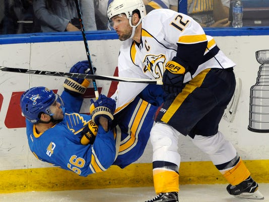 St. Louis Blues' Magnus Paajarvi (56), of Sweden, is checked by Nashville Predators' Mike Fisher (12) during the third period of an NHL hockey game, Sunday, April 2, 2017, in St. Louis. (AP Photo/Bill Boyce)