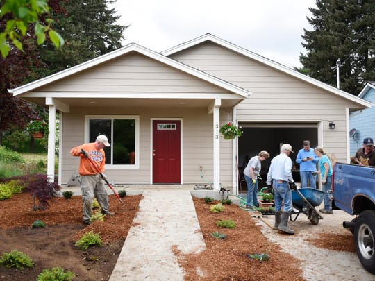 Volunteers finish the landscaping at a North Willamette Valley Habitat for Humanity home in Silverton on Wednesday, May 9, 2018. On May 16th, single mother, Kim Betker, and her 11-year-old son, Shawn, will receive the keys to their new home.