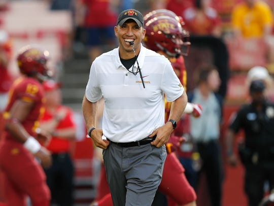 Iowa State coach Matt Campbell smiles as he walks on