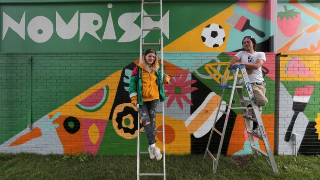 Jesse Kassel, 29, and Ellen Rutt, 26, both of Detroit  in front of their on their Nourish mural near shed 6 at the Detroit Eastern Market.  It was unveiled in a promotional event for the 2016 Murals in the Market.
