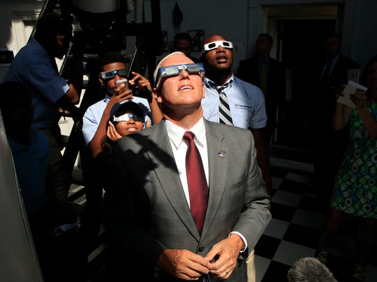 Vice President Mike Pence, with students from Cornerstone Schools, watches the solar eclipse, Monday, Aug. 21, 2017, at the U.S. Naval Observatory in Washington.