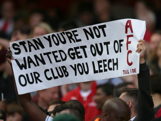 An Arsenal fan holds up a protest banner in reference to Arsenal majority owner Stan Kroenke, during the English Premier League soccer match between Arsenal and Everton at The Emirates stadium in London, Sunday May 21, 2017. (AP Photo/Tim Ireland)