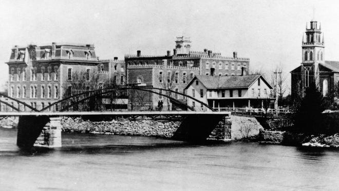 """This view of the original St. Mary Academy, constructed in 1880, also shows some of the other buildings that were part of the """"educational quad,"""" including a music hall and chapel. St. Mary Church is visible in the upper right-hand corner, along with the Monroe Street Bridge."""