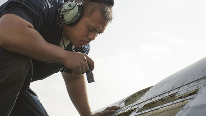 Tech. Sgt. Carlo Patalinghug, 455th Expeditionary Aircraft Maintenance Squadron crew chief, deployed from Hill Air Force Base, Utah, examines an F-16 Fighting Falcon.