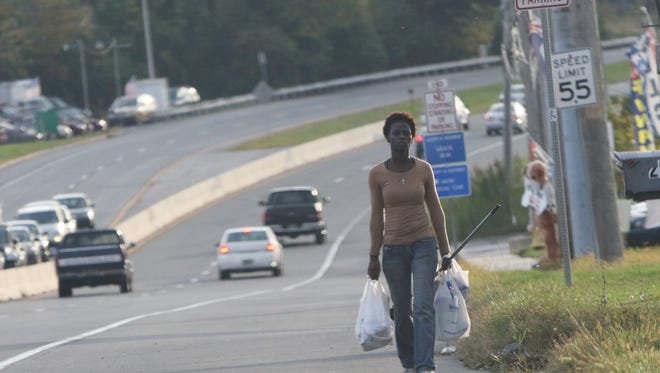 Shayné Jackson walks along U.S. 13, from Wal-Mart to the Hollywood Motel near New Castle in October. On Tuesday, state officials passed five recommendations to make walking safer in Delaware.