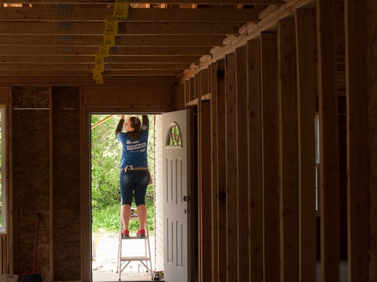 Habitat for Humanity volunteer, Aimee Priest hammers wood in the front entrance of a home on Tanyard Road in Deptford.