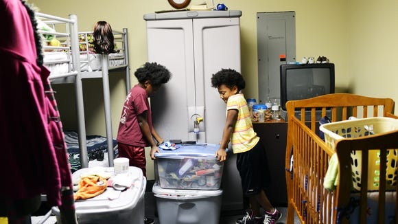 Aaliyah, 8, and Zahmari, 6, help each other close the bins that store their clothing and belongings at the shelter. Each family is allowed a certain number of bins. 6/16/14
