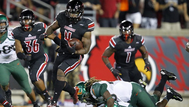 University of Louisville's Crovin Lamb (4) breaks free from University of Miami's Nantambu-Akill Fentress (28) as he runs the kick-off back for the touchdown during the first half of play at Papa John's Cardinal Stadium in Louisville, Kentucky.       September 1, 2014