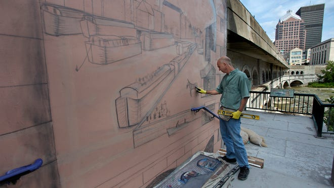 Syracuse mural artist Corky Goss is painting an Erie Canal mural with a scene from  1830's Rochester on a wall along the Broad Street  bridge next to Blue Cross Arena. The mural will be finished in the next couple of weeks. Goss' company is On Sight Murals of Syracuse.
